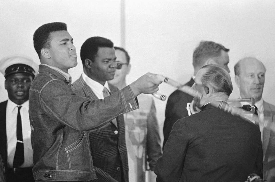 Cassius Clay waves his cane as he greeted