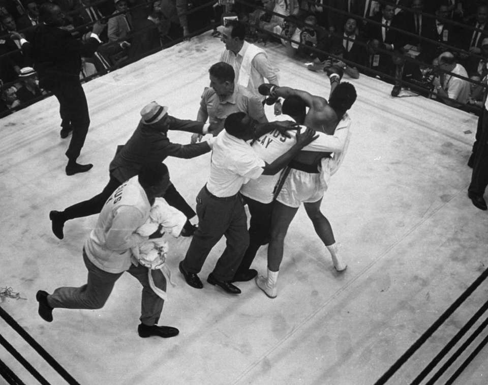 Handlers of Cassius Clay swarm over him in