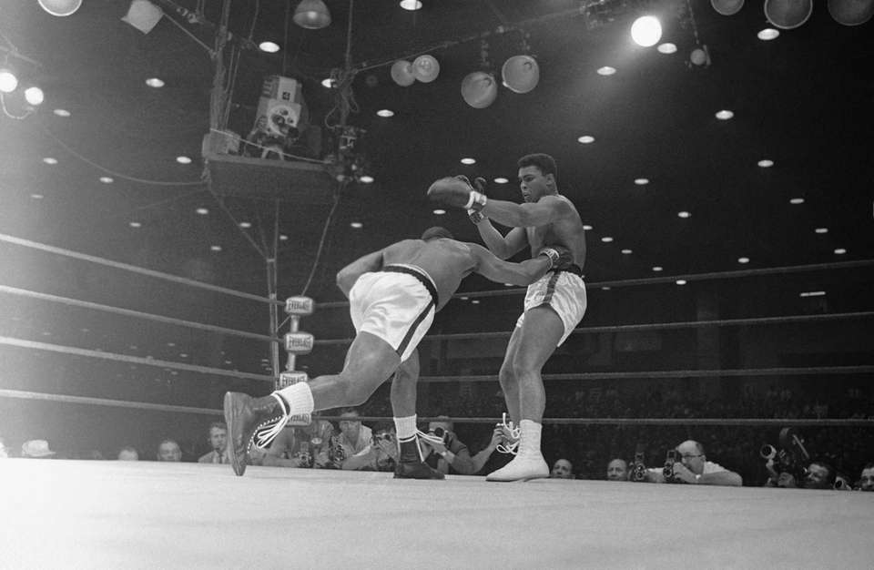 Champion Sonny Liston ducks under the outstretched gloves