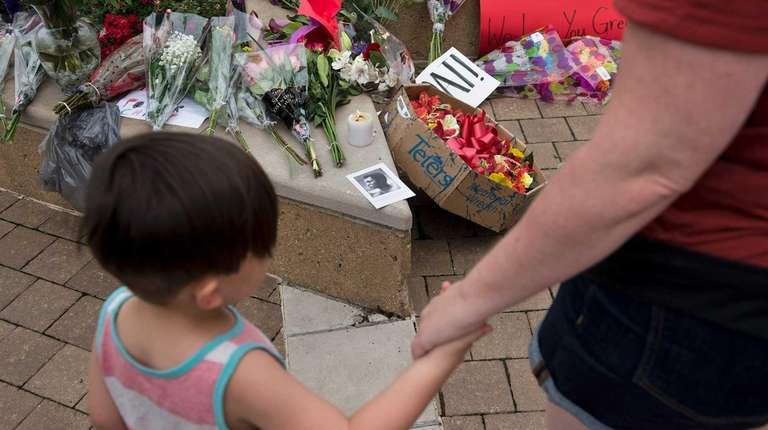 People pay respects at a makeshift memorial for
