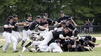 Wanthagh players pile on at the pitcher's mound