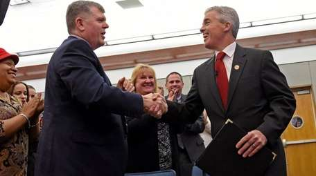 Suffolk County Executive Steve Bellone, right, is greeted