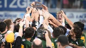 Ward Melville players reach for their championship plaque