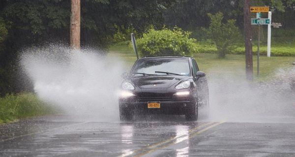 A car navigates a large puddle on Route
