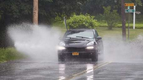 A car navigates a large puddle on Route