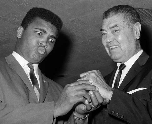 Heavyweight champion Muhammad Ali admires the fist of