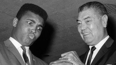 Heavyweight champion Muhammad Ali admires the fist of