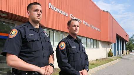 Nassau County Police Officer Ronald Curaba, left, and