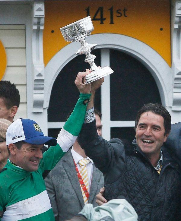Jocky Kent Desormeaux, left, holds a trophy with