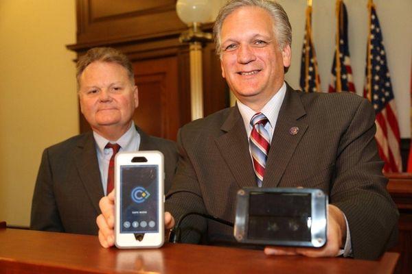 Nassau County Executive Edward Mangano holds a device
