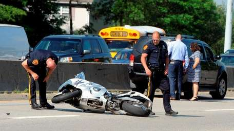Suffolk police investigators look over a motorcycle that