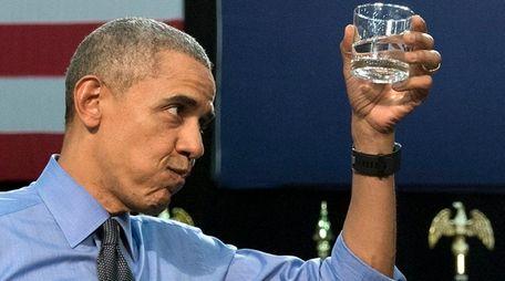 President Barack Obama holds up a glass of