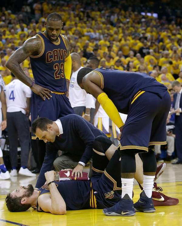 A trainer checks on Cleveland Cavaliers forward Kevin