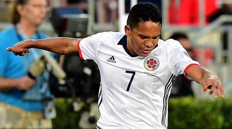 Colombia's Carlos Bacca, left, vies for the ball