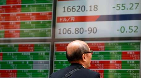 A man watches an electronic stock board showing
