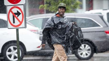 A man copes with the rain by wrapping