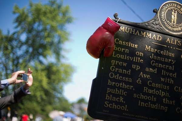 Boxing gloves hang on a historical marker outside