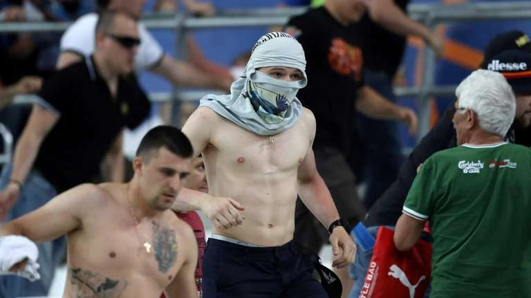 People leave the stadium following clashes between Russian