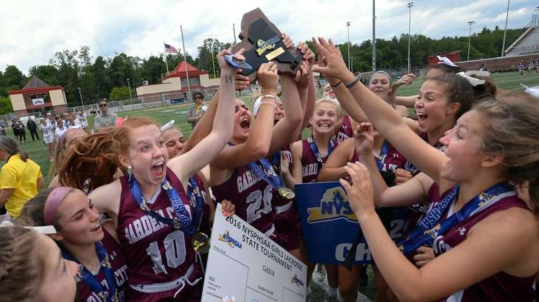 Garden City players raise the championship plaque following