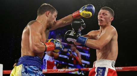 Vasyl Lomachenko, left, of Ukraine, punches Roman Martinez,