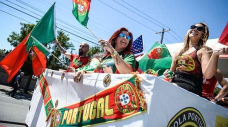 People on the Mineola Portuguese Center float wave