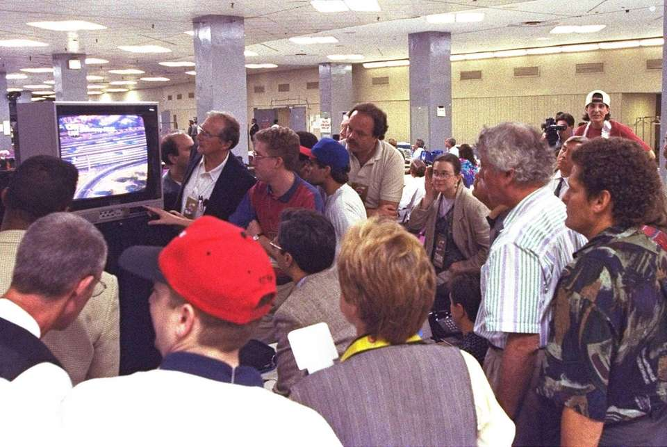Members of the news media watch live television