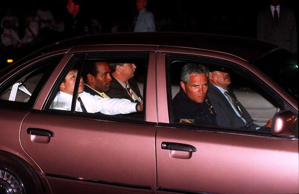 O.J. Simpson, center of rear seat, rides into