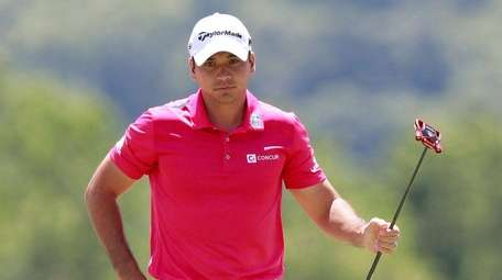 Jason Day stands on the third green during