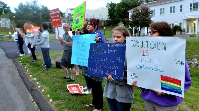 Protesters hold signs Sunday in front of the