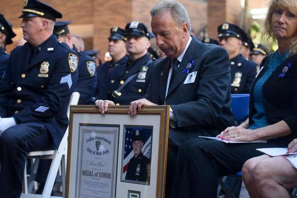 Retired NYPD Sgt. Raymond Moore, holds a framed