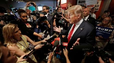 Donald Trump answers questions from reporters after