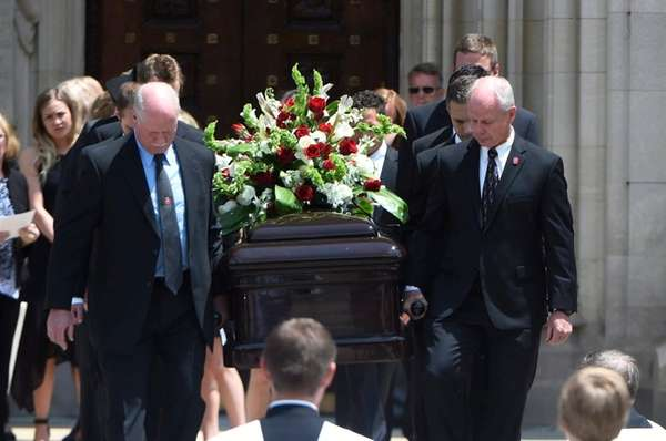 Pallbearers carry the casket out of the cathedral
