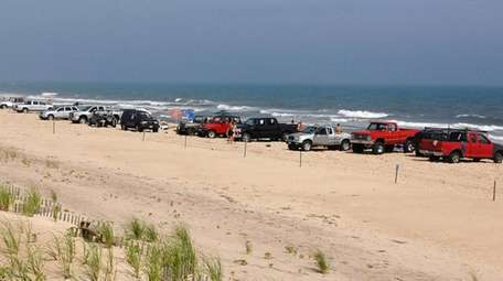 Vehicles line the beach known as