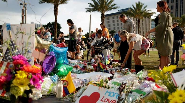 People visit the makeshift memorial for the victims