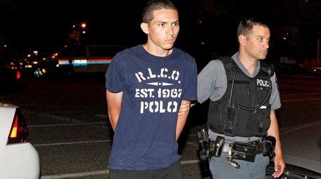 Evilson Orellana, 18, of Hempstead, is taken into