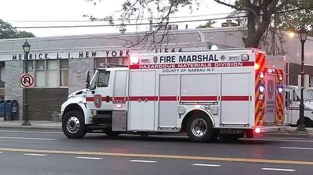Firefighters and a Nassau County Fire Marshal's Office