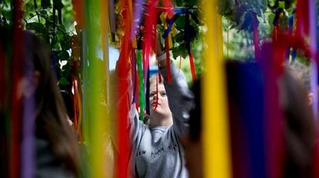 People place rainbow-colored ribbons on the Survivor Tree
