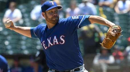 Colby Lewis of the Texas Rangers pitches against