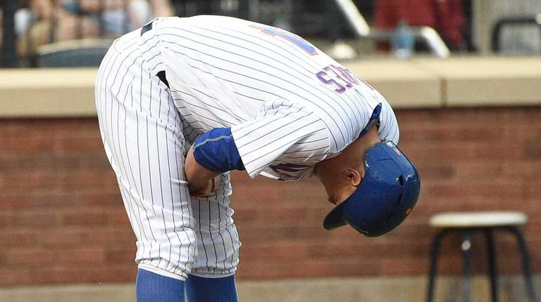 Mets third baseman Wilmer Flores reacts after he