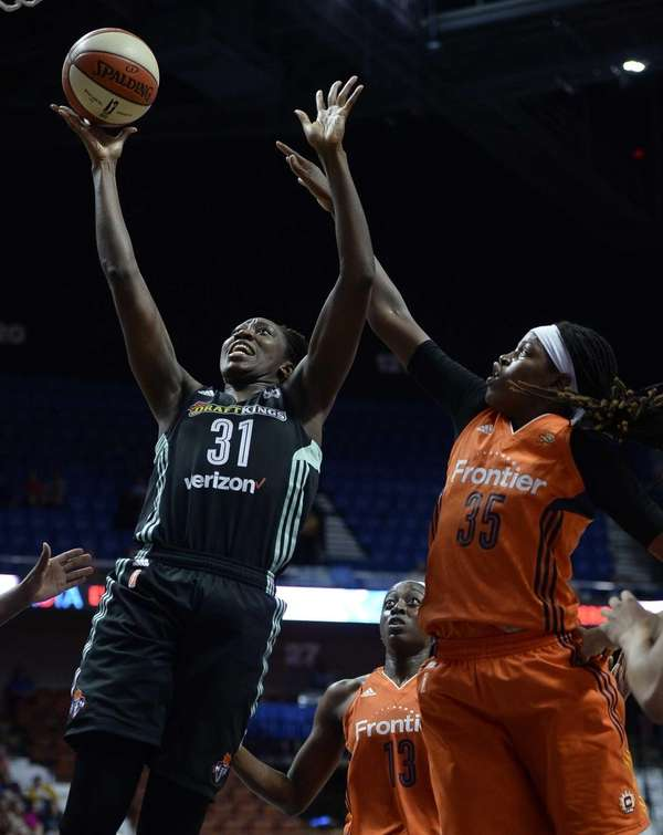 New York Liberty's Tina Charles, left, shoots over