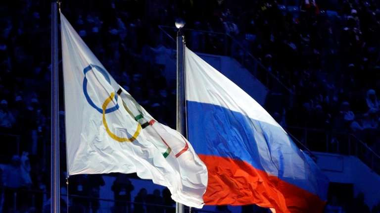 The Russian and the Olympic flags wave during