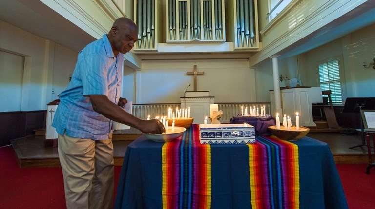 Congregation member Willie White lights a candle in