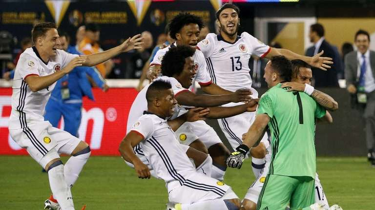 Colombia's goalkeeper David Ospina (R) celebrates with teammates