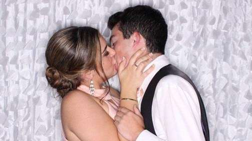 A couple shares a kiss in the photo