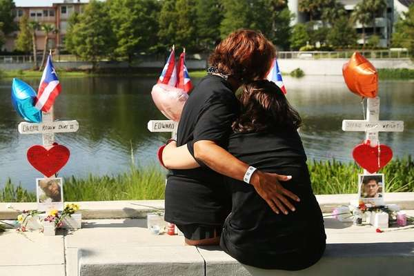 Two women embrace beside a memorial down the