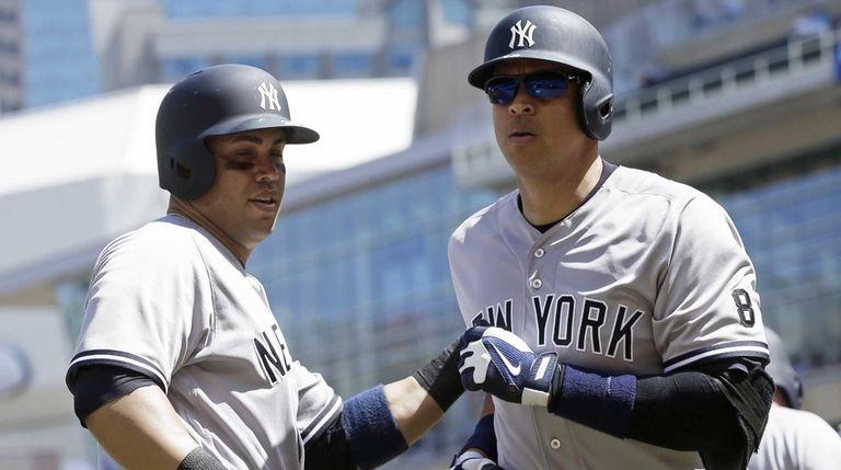 New York Yankees' Alex Rodriguez, right, gets congratulations