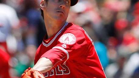 Angels pitcher Tim Lincecum throws to the A's