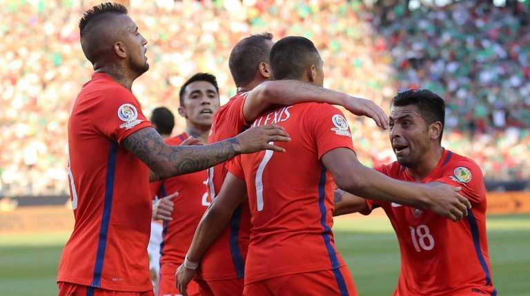 Chilean footballers celebrate after scoring against Mexico during
