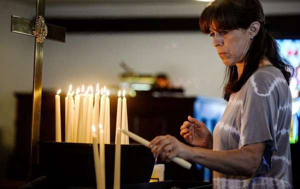 Susan Oldis of Rockville Centre lights a candle