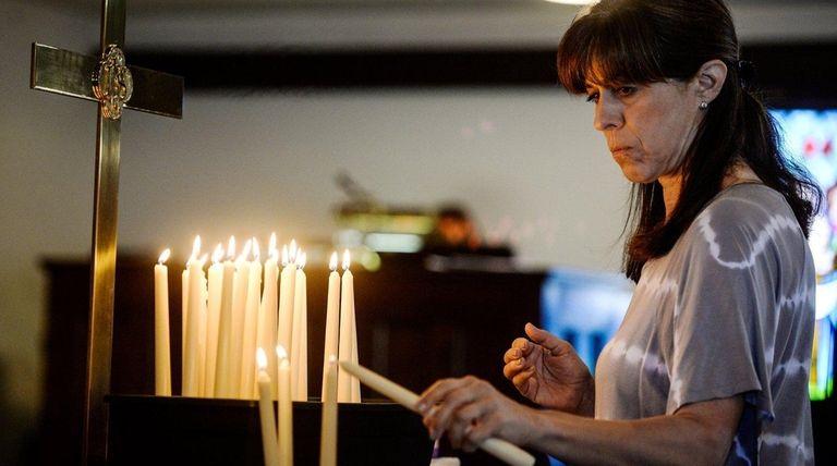 Susan Oldis of Rockville Centre lights a candle